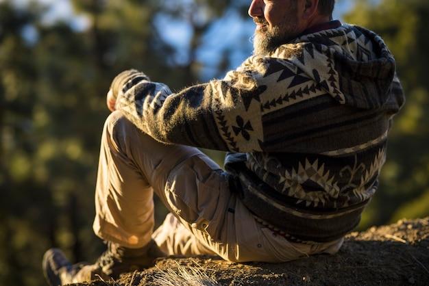 岩だらけの丘から風光明媚な森をリラックスして眺める男の背中。丘の上から森の景色を眺めるハイカー。休憩して丘の上でリラックスする観光客