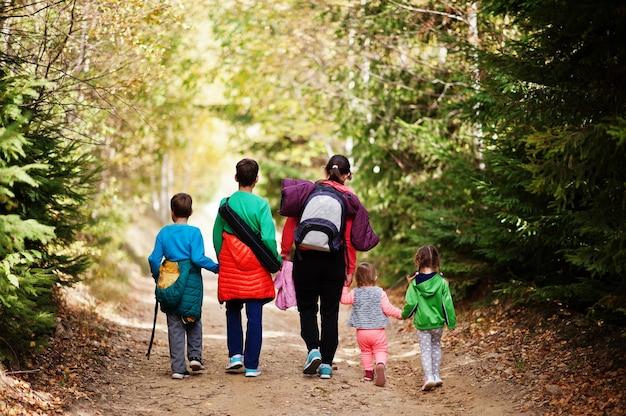 木の山を歩いている4人の子供を持つ母の背中。家族旅行や子供とのハイキング。バックパックを着用してください。