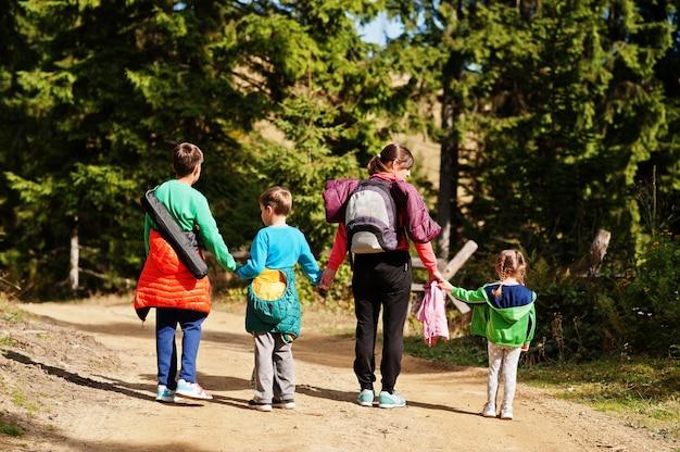 木の山を歩いている3人の子供を持つ母の背中。家族旅行や子供とのハイキング。