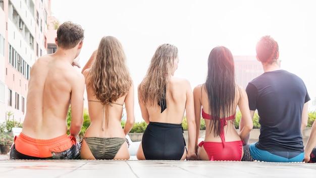 Назад людей на плавание одежды, сидя у бассейна воды, наслаждаясь отдыхом