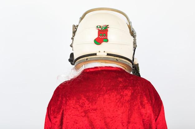Спина санта-клауса в шлеме космонавта с рождественским орнаментом на белом фоне