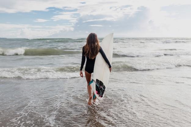 서핑 보드를 들고 바다에 들어가는 슬림 한 여성의 뒷면