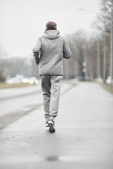 寒い秋に一人でトレーニングしながら道路に沿って走っている灰色のスポーツスーツのスポーティな老人の背中