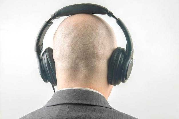 音楽を聴いてリラックスしてヘッドフォンを持っている男の頭の後ろ
