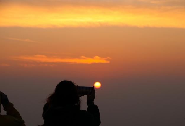 Спина туриста, делающего фотографию умным телефоном восход и пейзажный вид