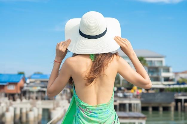白い帽子を持つ旅行女性の裏はビーチと青い空でリラックス