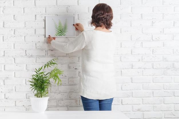 壁に彼女のスケッチをぶら下げ女性裏。女性アーティストは、白いレンガの壁、テキスト用の空きスペースで試して、彼女の絵画のパフォーマンスを評価します