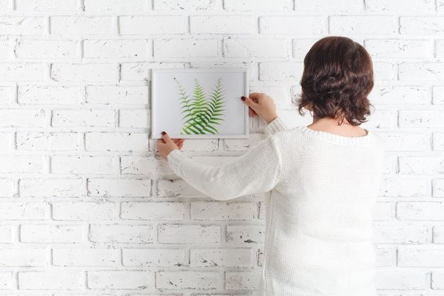 壁に彼女のスケッチをぶら下げ女性裏。