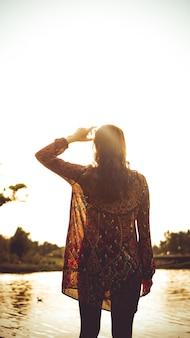 Спина женщины, отдыхающей на природе у реки. солнечный день кипения