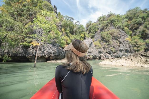 Спина женщины-туристки на красном каяке в ко хонг, пещера тхам лот на острове хонг в заливе пханг-нга, таиланд.