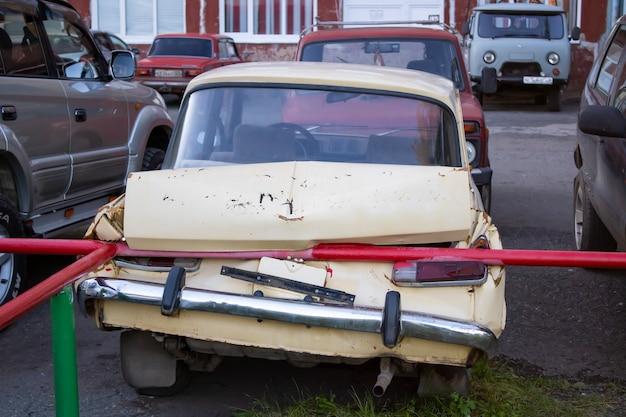 黄色い色の車の後ろが大きな損傷を受け、都市の駐車場で偶然に壊れて、もう運転できません