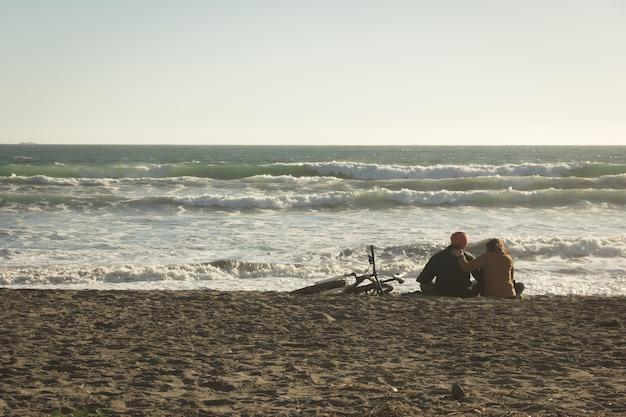 チリ、ラセレナの空のビーチの砂に沈む夕日を楽しんで愛する若いカップルの背中