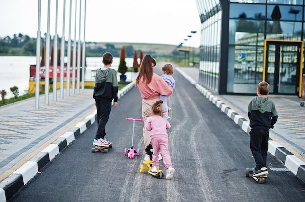 屋外で4人の子供を持つ若いスタイリッシュな母親の背中。スポーツの家族は、スクーターやスケートで屋外で自由な時間を過ごします。