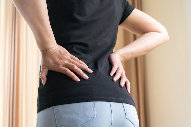 自宅での腰痛。女性は腰痛に苦しんでいます。ヘルスケアと医療の概念