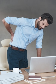 Back pain. frustrated young handsome man looking exhausted while massaging his back