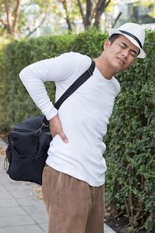 重いバッグを運ぶ背中の痛みの男