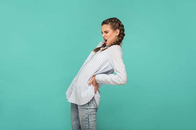 Боль в спине, профиль вида сбоку портрет несчастной грустной девушки в синей полосатой футболке и косичке с волосами, стоя и чувствуя боль на спине или почках. крытая студия выстрел, изолированные на зеленом фоне.