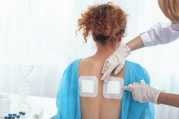 허리 통증 완화. 전문 의사가 검사하는 그녀의 통증에 대한 열 고약을 여전히 받고있는 어린 소녀