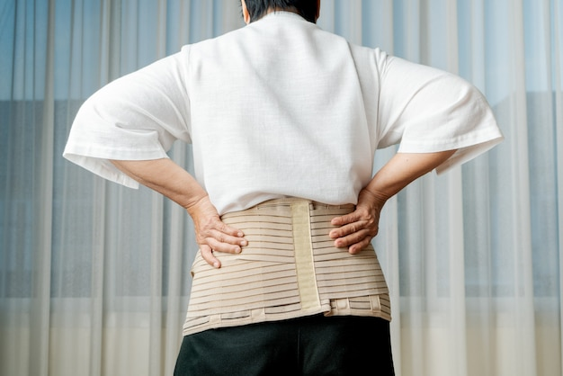 Back pain, senior woman wearing back support belt on white background