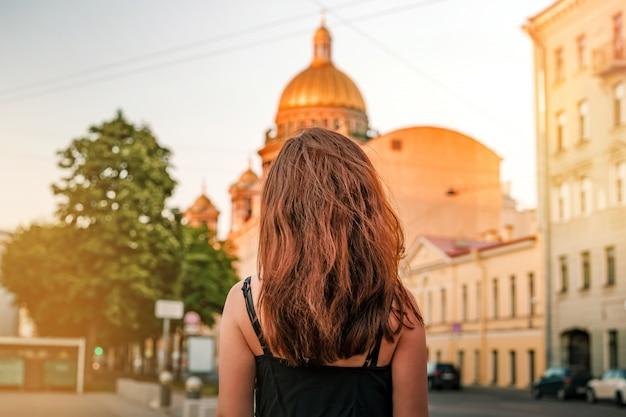 ピーターズバーグの聖イサアク大聖堂を背景に長い髪の少女の裏写真