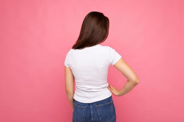 コピースペースでピンクの背景の上に分離されたモックアップの白いtシャツを着ているブルネットの女性のバック写真ショット。
