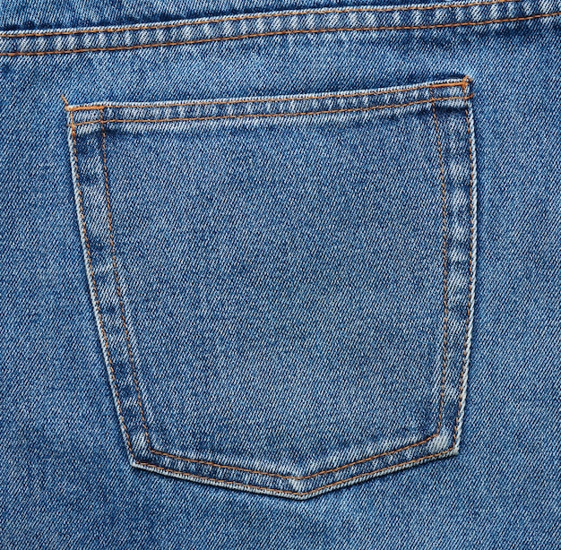 Back pocket of blue jeans with brown thread seams