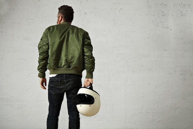 Back portrait of a hip bearded pilot in green bomber jacket, skinny jeans and with a white blank helmet in his hand with white walls