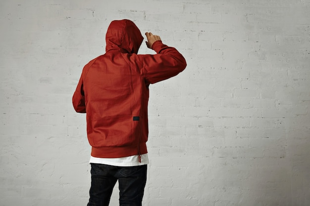 Back portrait of a man in black jeans, white t-shirt and red parka putting on his hood on white wall