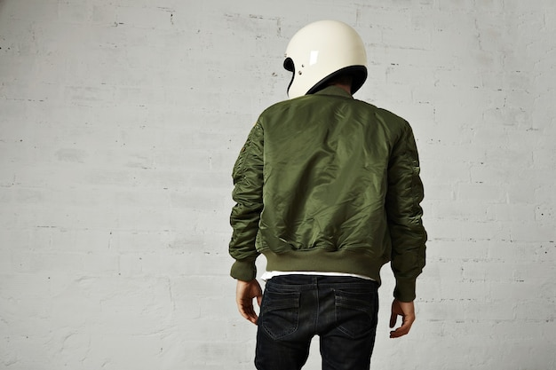 Back portrait of a motorcyclist in white helmet and green bomber jacket isolated on white
