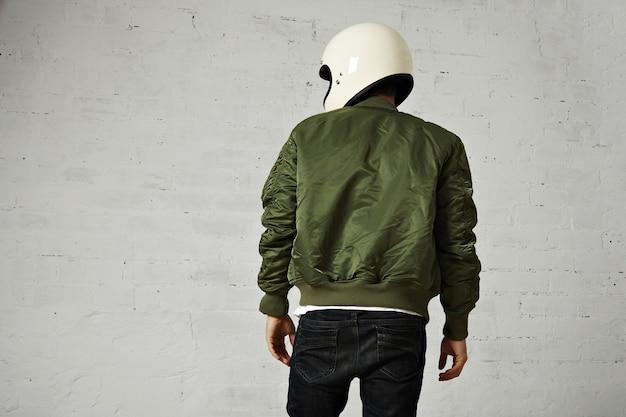 Задний портрет мотоциклиста в белом шлеме и зеленой куртке бомбардировщика, изолированные на белом