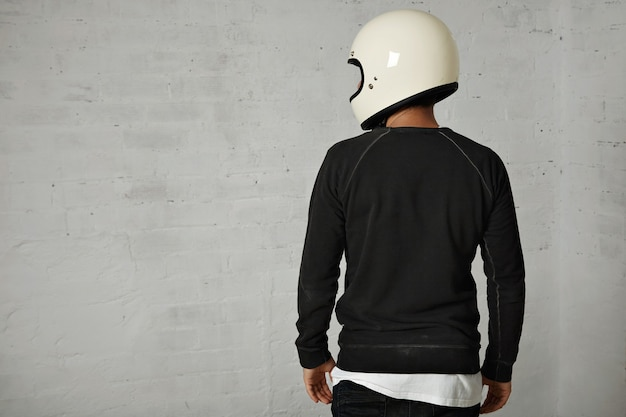 白で隔離の光沢のある白い空白のオートバイのヘルメットを身に着けている黒と白のカジュアルな服を着た若い男の肖像画