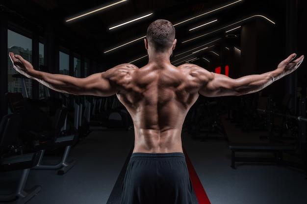 Задний портрет спортивного мускулистого мужчины в тренажерном зале. концепция фитнеса.
