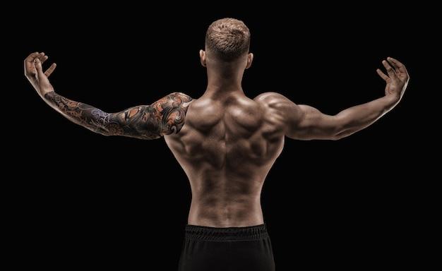 Задний портрет спортивного мускулистого мужчины в студии. концепция фитнеса. смешанная техника