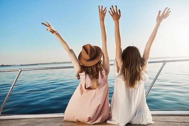 ヨットの側に座って手を振って、海辺を見ながら幸せを表現するドレスを着た2人の女性の後ろ姿。一緒に旅行する親友よりも上手に応援できる人