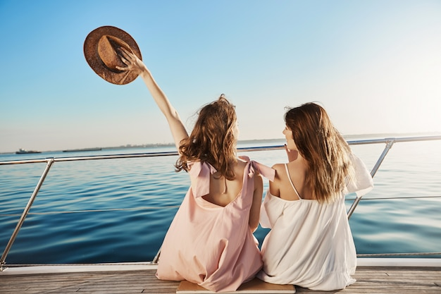 Back portrait of two female friends sitting on boat, waving with hat while talking and enjoying looking at seaside. sisters finally took vacation to visit their mom who lives in italy