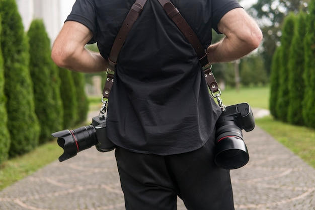 Back of professional photographer in black shirt and with a two cameras an a shoulder straps against the green garden.