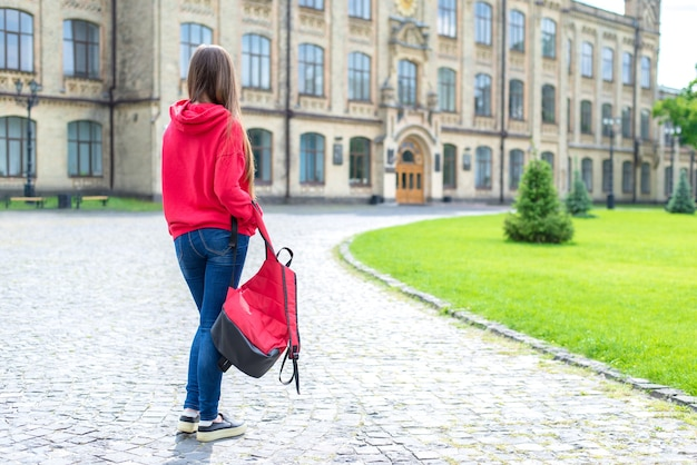Back rear behind full body length size photo of sad upset unhappy teenager teen hipster wearing sneakers holding carelessly her bright schoolbag looking at the doors