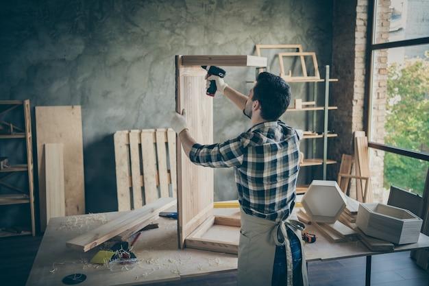 Задняя задняя сторона сфокусирована на профессиональном работнике из твердых пород дерева, который исправляет стол для плиты, используется электронная дрель, требуется ремонт декоративной мебели в домашнем гараже