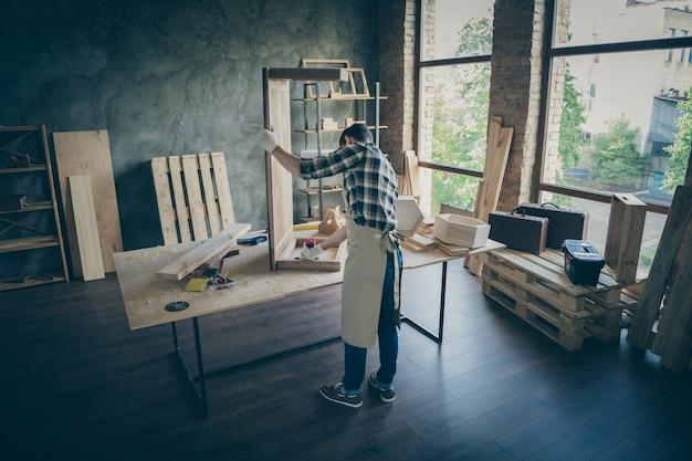 Задняя задняя сторона полная длина сконцентрированный работник ручной работы предприниматель возобновляет плиточный стол использовать дрель исправить изделия из дерева в домашнем гараже