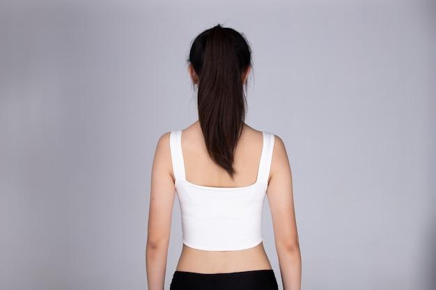 アジアの人々の背面背面図は、ストレートの黒いポニーテールのヘアスタイルを提示し、スポーツブラのフィットネスドレスで女性の髪を包みます