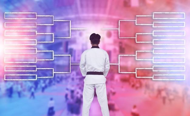 마스터 블랙 벨트 운동 선수의 후면 보기 일정 또는 도면 차트를 통해 남자는 빨간색 파란색 스포츠 개념의 준준결승에서 싸우는 태권도, 가라테, 유도의 전략을 계획할 수 있습니다.