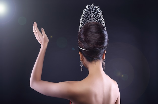 Back rear side view portrait of miss pageant beauty contest with diamond crown wave hand