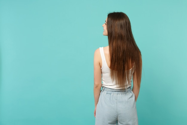 Back rear view of attractive young woman in light casual clothes looking aside isolated on blue turquoise wall background in studio. people sincere emotions, lifestyle concept. mock up copy space.