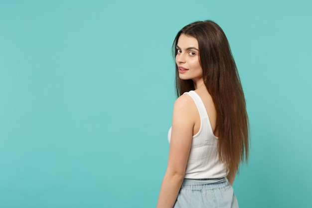 Back rear view of beautiful cute young woman in light casual clothes looking back isolated on blue turquoise wall background in studio. people sincere emotions, lifestyle concept. mock up copy space.
