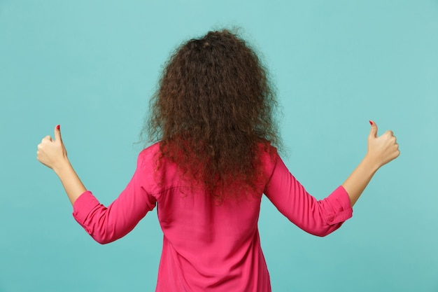 ピンクのカジュアルな服を着たアフリカの女の子の背面図は、スタジオで青いターコイズブルーの背景に分離された親指を示しています。人々の誠実な感情のライフスタイルの概念。コピースペースをモックアップします。