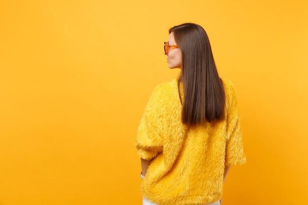 毛皮のセーター、明るい黄色の背景で隔離の脇を探しているオレンジ色の眼鏡のブルネットの若い女性の背面背面図。人々の誠実な感情、ライフスタイルのコンセプト。広告用のスペースをコピーします。