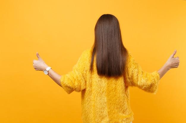 Вид сзади молодой женщины брюнет в меховом свитере, разводя руками, показывая большие пальцы руки вверх, изолированные на ярко-желтом фоне. люди искренние эмоции, концепция образа жизни. скопируйте место для рекламы.