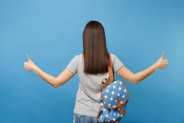 Вид сзади молодой студентки брюнетки в повседневной одежде с положением рюкзака, показывая большие пальцы руки вверх, изолированные на синем фоне. обучение в университетском колледже. скопируйте место для рекламы.