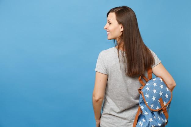 Вид сзади молодой улыбающейся студентки брюнетки в повседневной одежде с рюкзаком, смотрящей в сторону, изолированной на синем фоне. образование в высшей школе вуза. скопируйте место для рекламы.