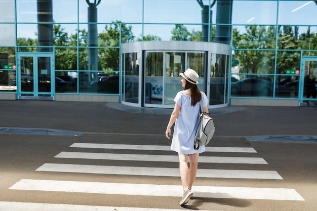 Вид сзади молодой улыбающейся туристической женщины путешественника в шляпе с рюкзаком, стоящей на пешеходном переходе в международном аэропорту